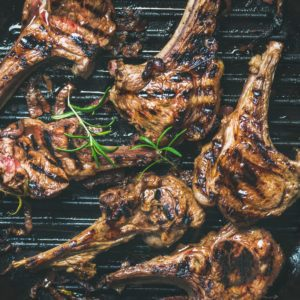 Grilled lamb meat chops with onion and rosemary in black cast iron pan, top view, close-up.