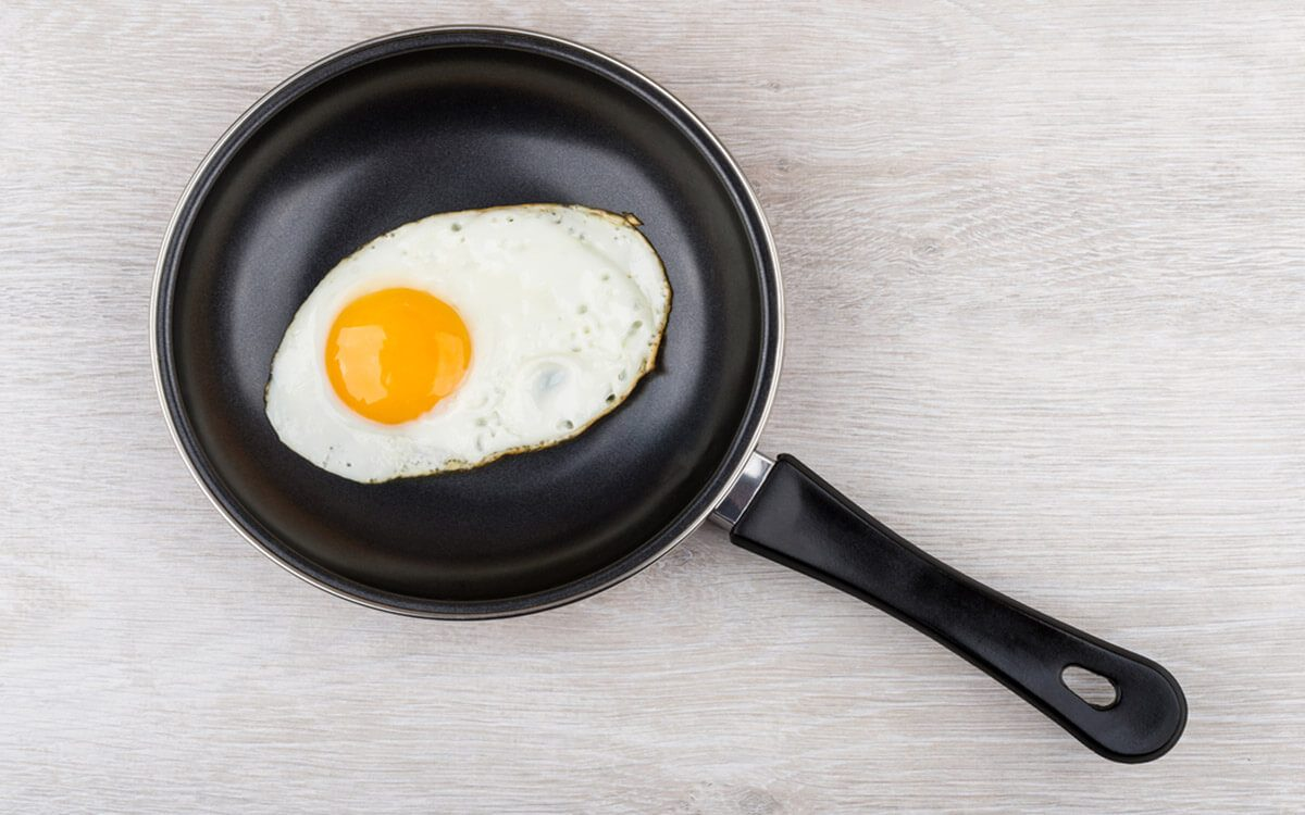 Fried egg in frying pan on wooden table