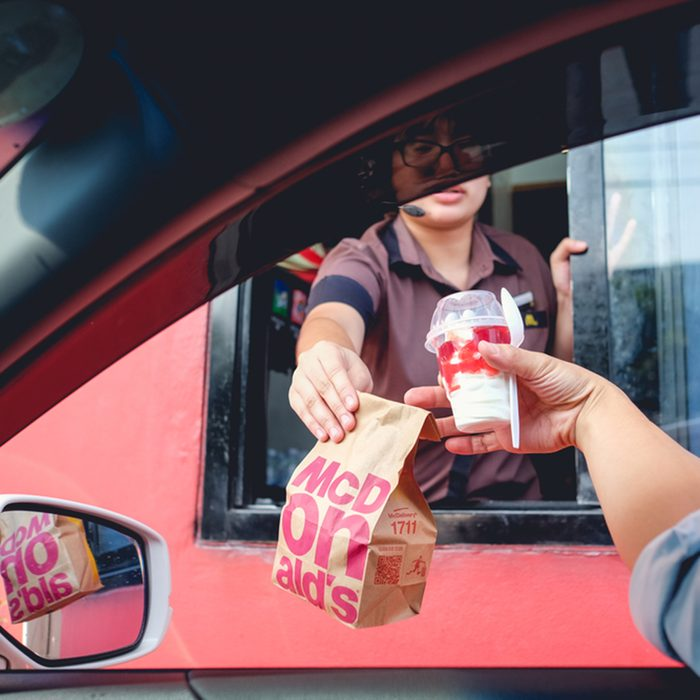 Bangkok, Thailand - Mar 4, 2017: Unidentified customer receiving hamburger and ice cream after order and buy it from McDonald's drive thru service, McDonald's is an American fast food restaurant chain; Shutterstock ID 598333484