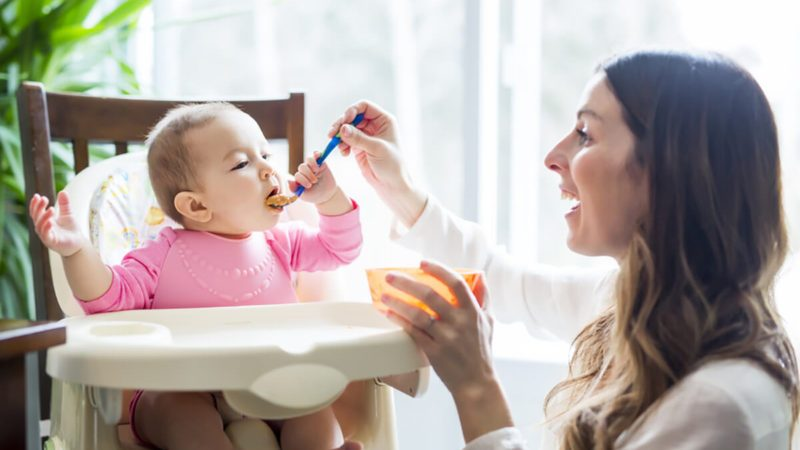 Young Mom Feeding Homemade Baby Food to Daughter in High Chair