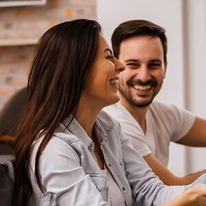 Young couple smiling and having fun at home