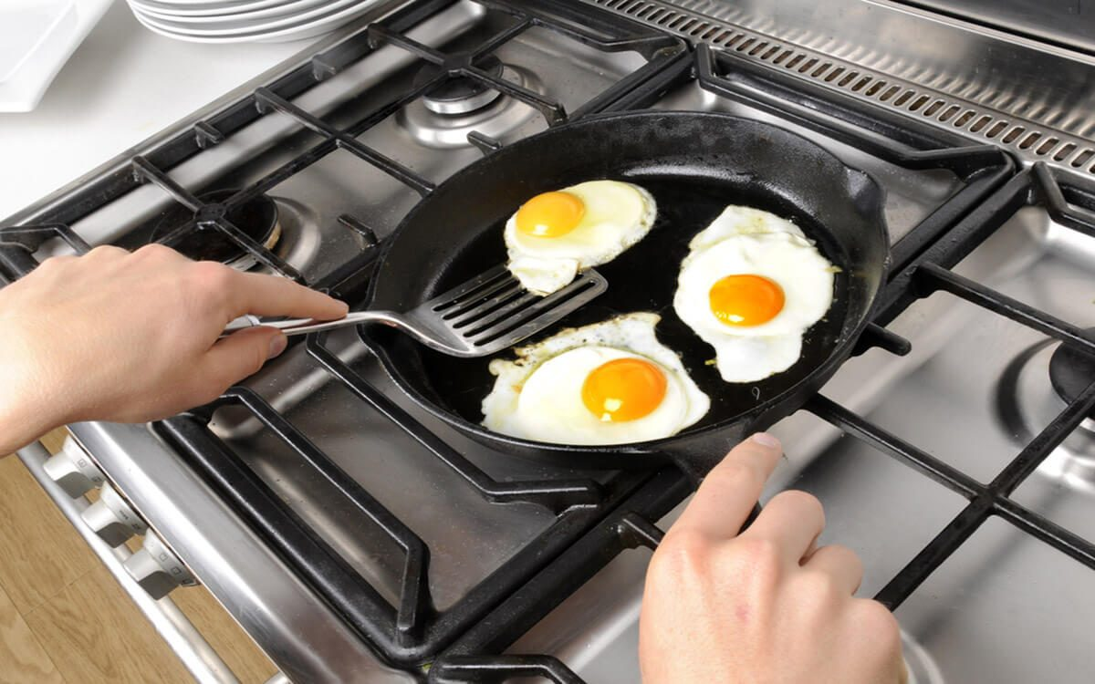 MAN FRYING THREE FRIED EGGD IN FRYING PAN ON COOKER HOB