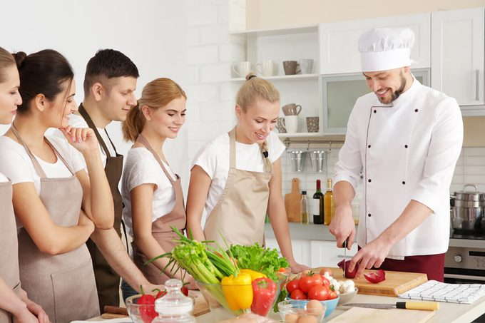 Male chef and group of people at cooking classes