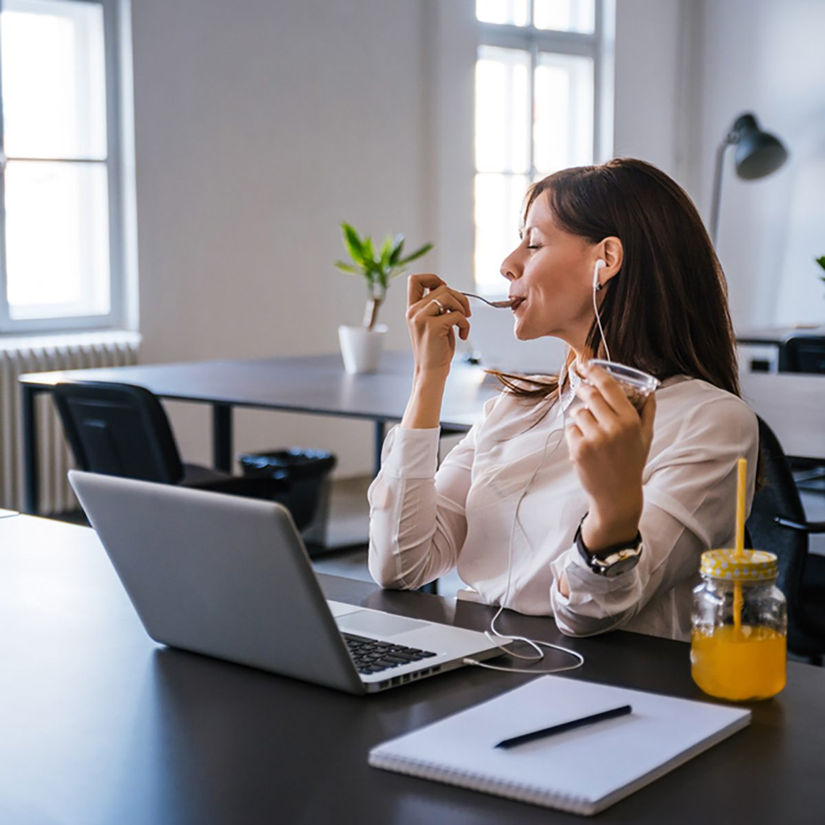 Woman relaxing after work, eating ice cream and listening to music