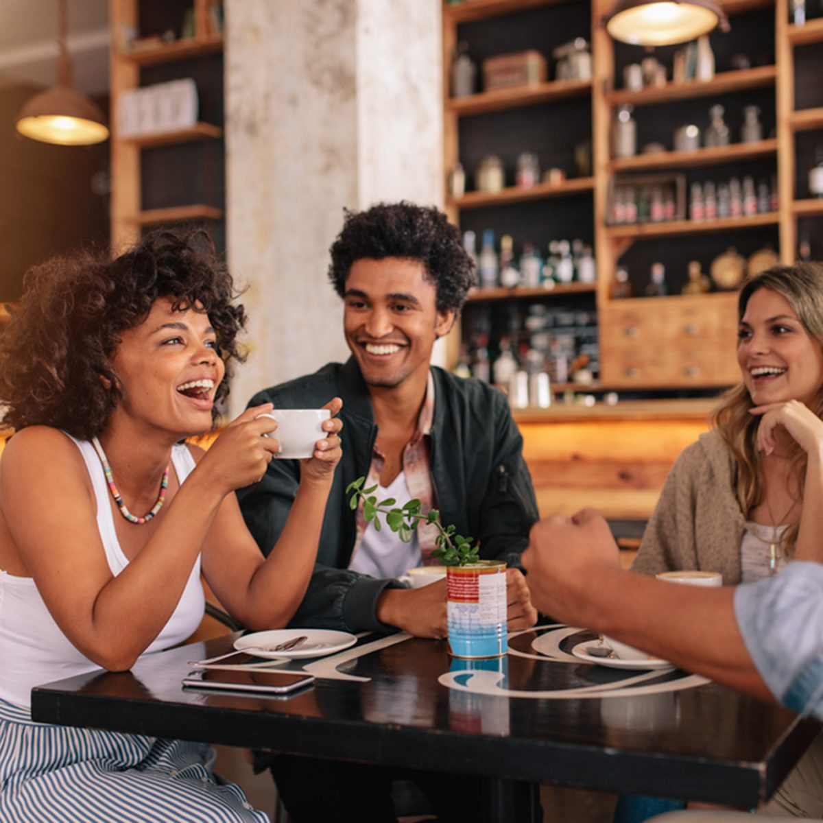Young friends having a great time in restaurant. Multiracial group of young people sitting in a coffee shop and smiling.; Shutterstock ID 661377859