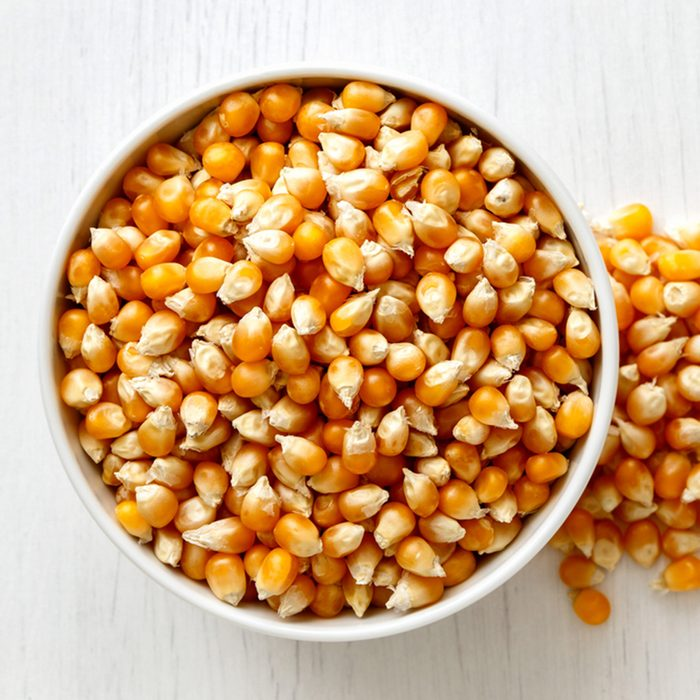 Unpopped popcorn in white ceramic bowl isolated on painted white wood from above. Spilled popcorn.; Shutterstock ID 664547797; Job (TFH, TOH, RD, BNB, CWM, CM): Taste of Home