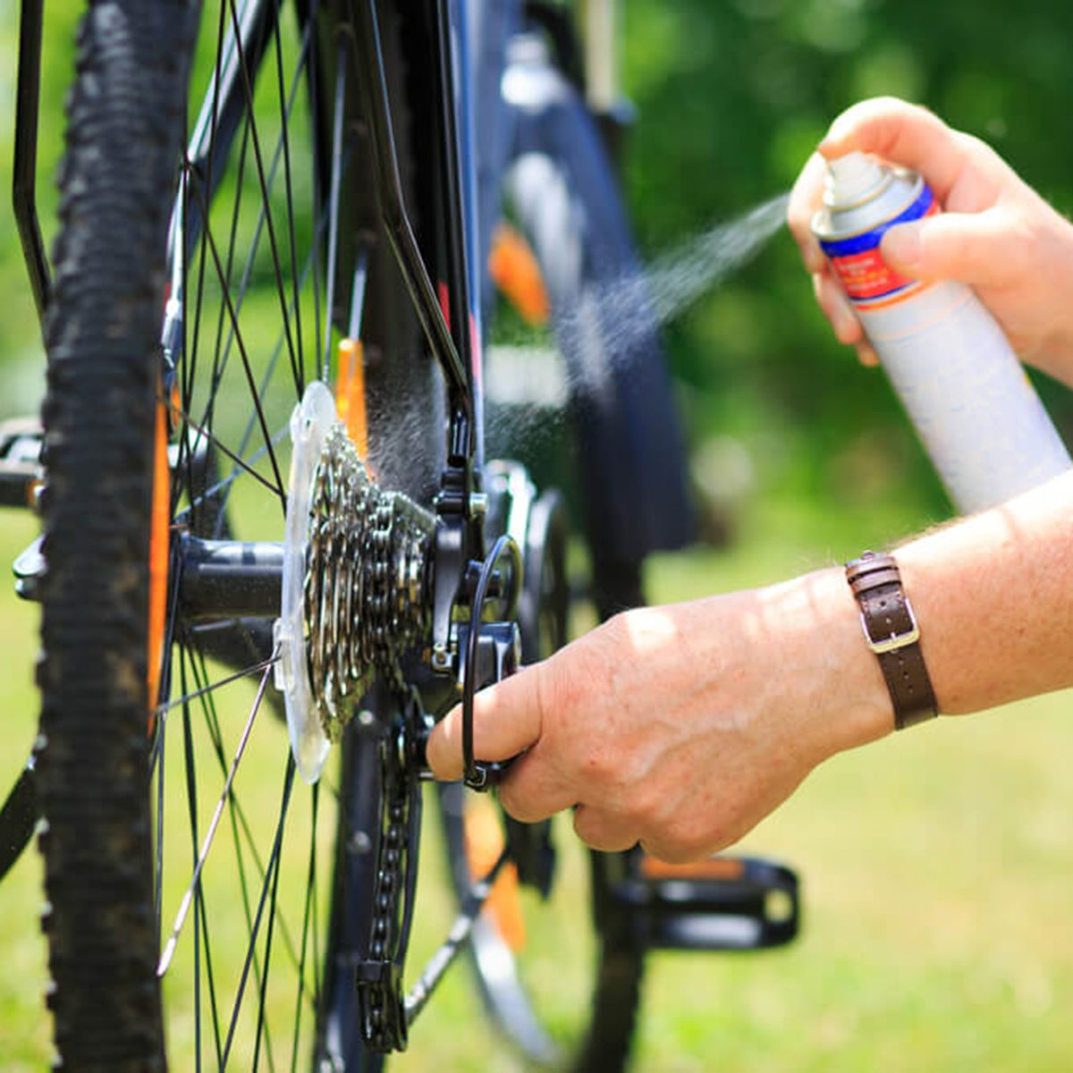 Man spraying oil on bike