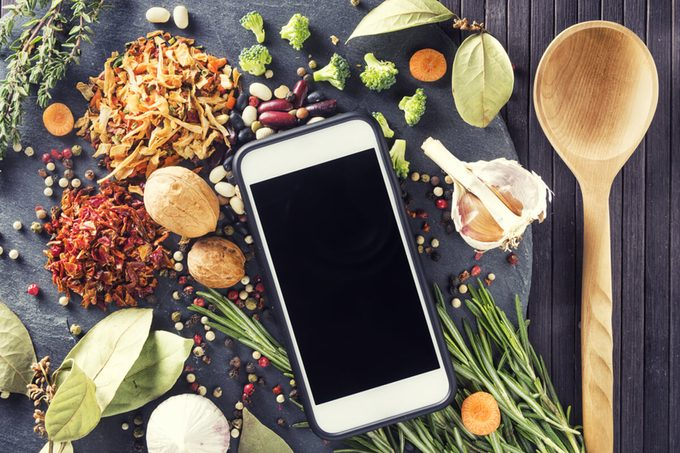 Kitchen table with ingredients, utensils and smartphone with blank screen for your app over cooking book on wooden table.
