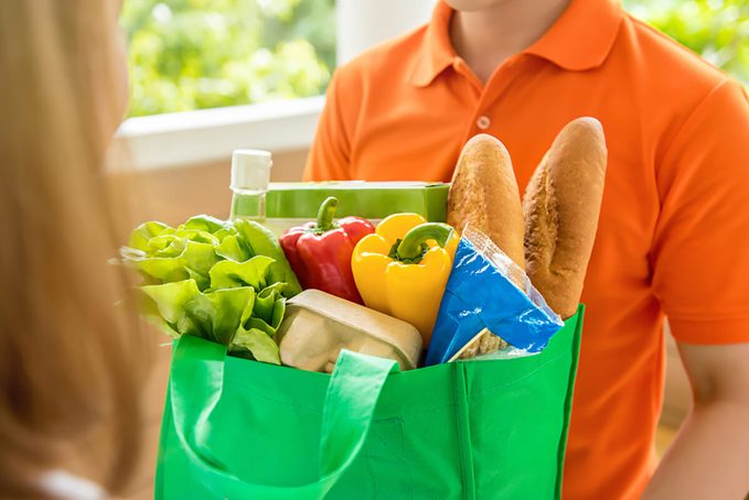 Grocery store delivery man wearing orange polo-shirt delivering food to a woman at home