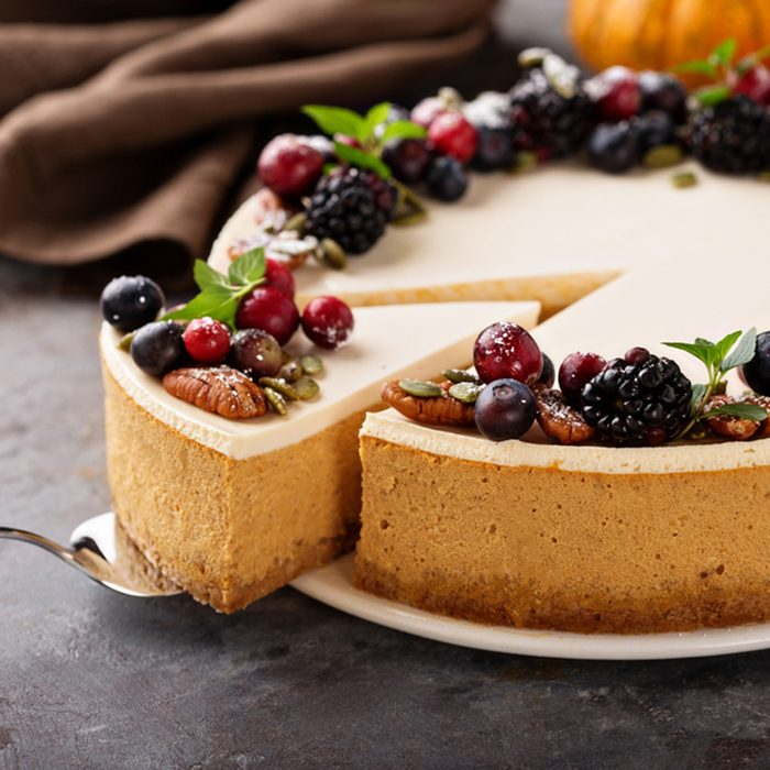 Pumpkin cheesecake with sour cream topping and fresh seasonal berries and nuts with a slice taken out; Shutterstock ID 751278079; Job (TFH, TOH, RD, BNB, CWM, CM): TOH