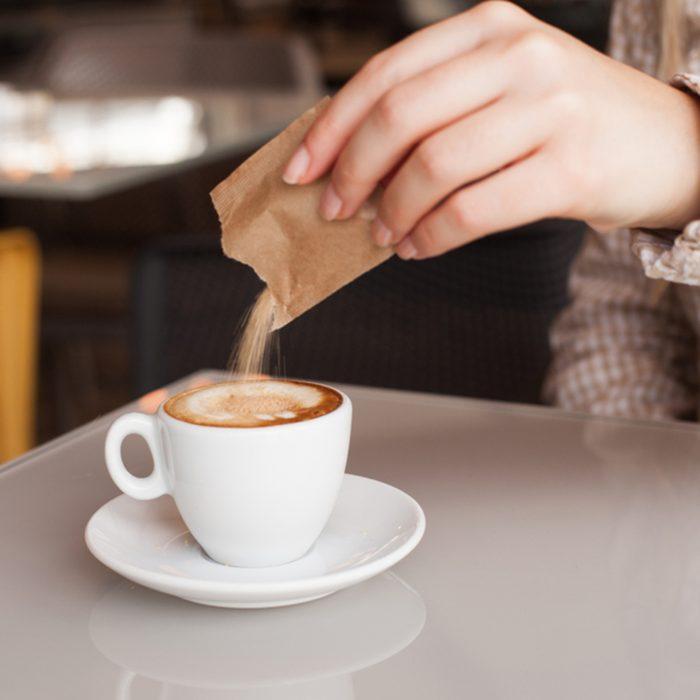 Woman hand adding sugar in coffee; Shutterstock ID 768253051