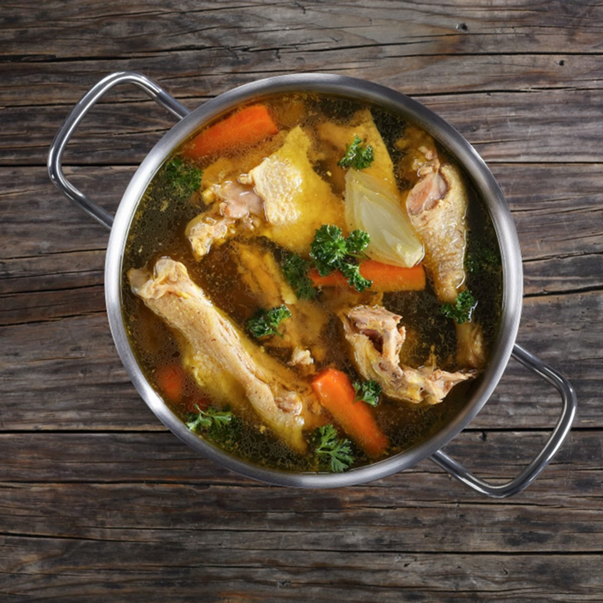 clear Chicken broth with pieces of rooster meat on bone and vegetables in a metal casserole on dark wooden table, view from above; Shutterstock ID 776860549