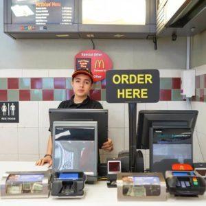Fast food worker behind the register