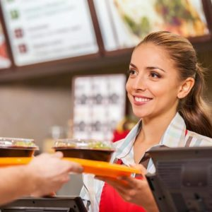Fast food worker handing a tray of food to a customer