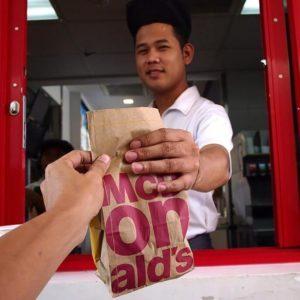 Fast food worker handing a drive-thru customer their bag of food