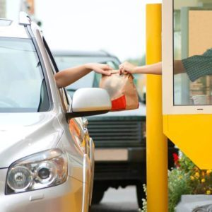 Fast food bag being handed out of a drive-thru window