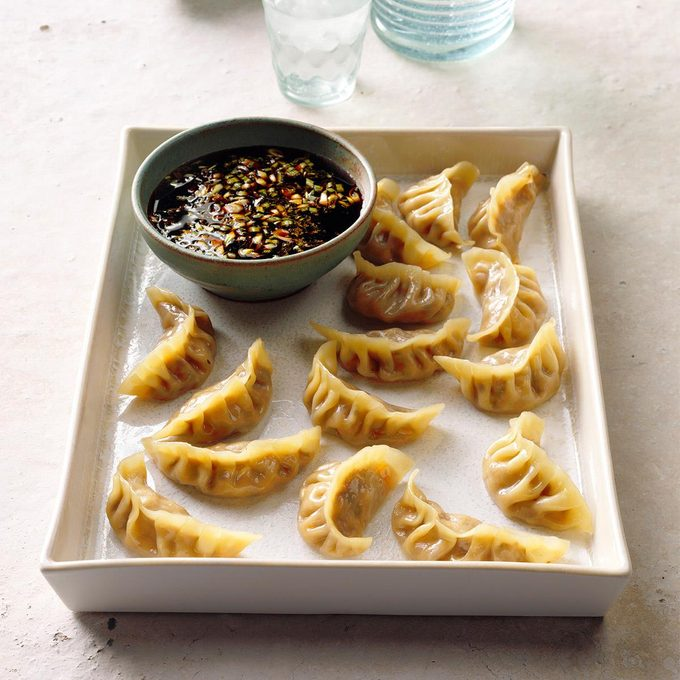 A tray of chicken pot stickers with dipping sauce.