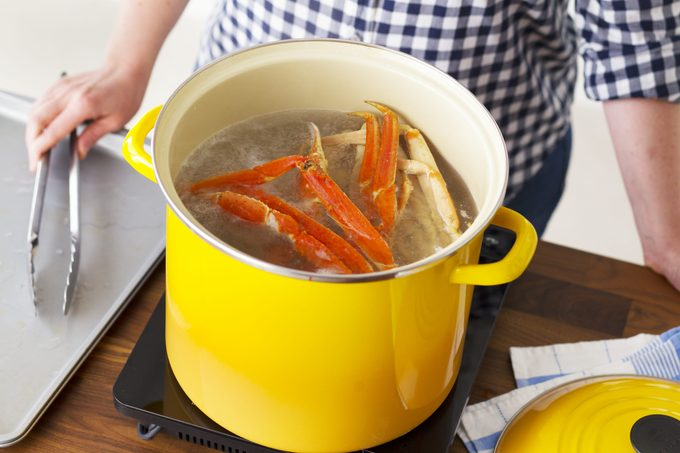 Crab legs boiling in a bright yellow pot