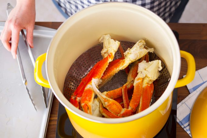 Steaming crab legs in a bright yellow pot