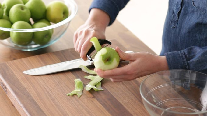Person peeling a green apple