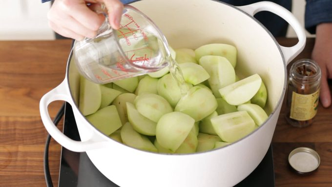 Person pouring water over peeled apples in a dutch oven