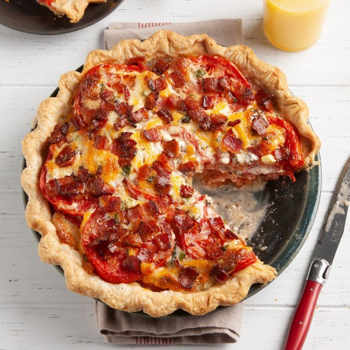 A tomato pie with one slice taken out of it.