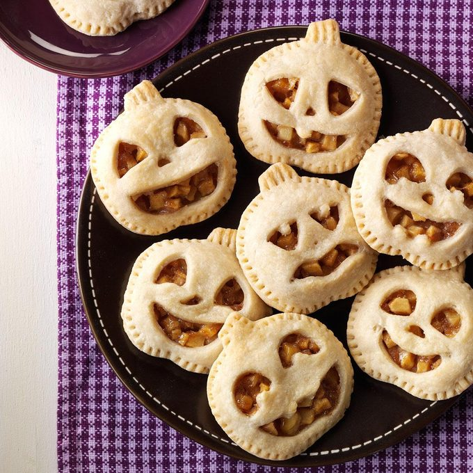 Mini pumpkin maple pies in the shape of jack-o-laterns arranged on a plate