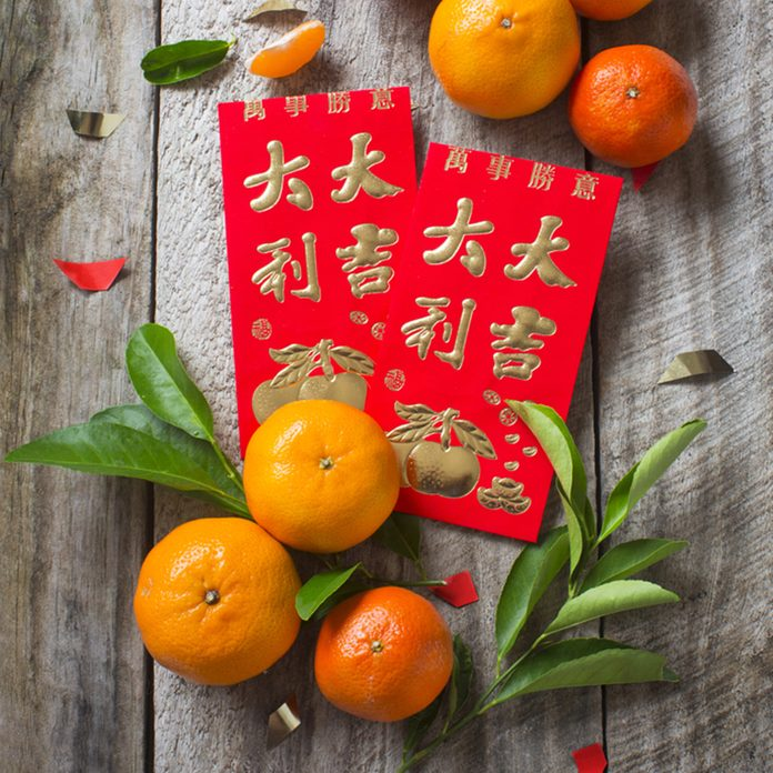 """Mandarin oranges and Chinese new year red packet with text """"Good luck and Great fortune"""" and smaller text """"All the Best"""" printed placed on rustic wooden background.; Shutterstock ID 361980683"""