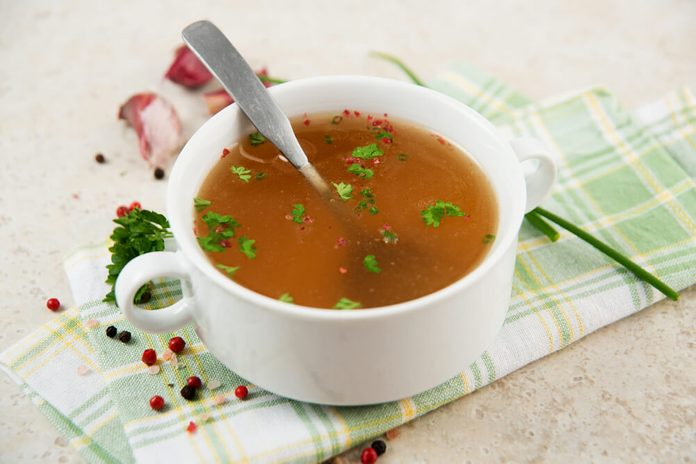 Bone Broth in Small Soup Bowl Served with Fresh Herbs, Garlic and Spices