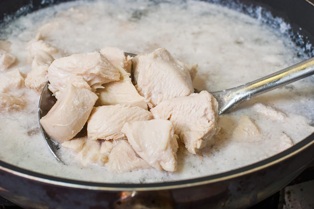 Boiled chicken breast in a pan on the sieve