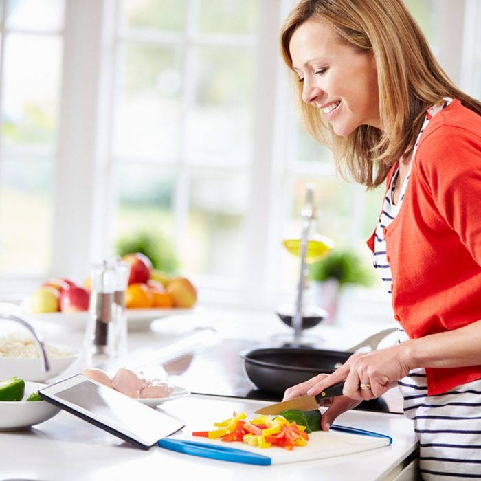 Woman In Kitchen Following Recipe On Digital Tablet; Shutterstock ID 165369422; Job (TFH, TOH, RD, BNB, CWM, CM): Taste of Home