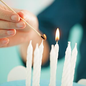 Woman lighting the candels on a birthday cake.
