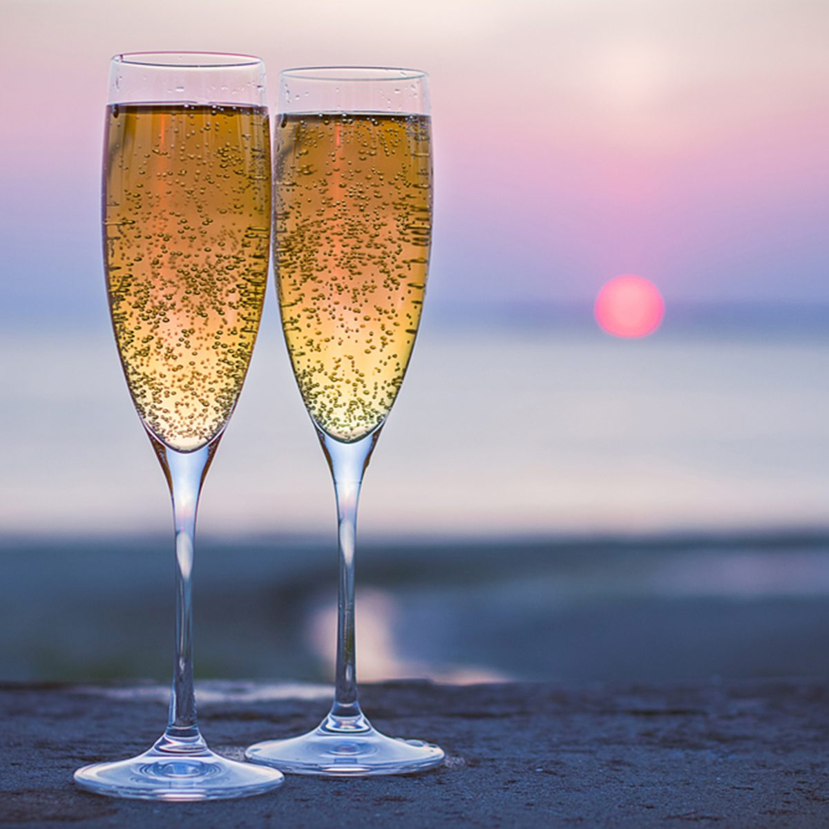 Two glasses of sparkling wine at sunset on the sea ; Shutterstock ID 213744382; Job (TFH, TOH, RD, BNB, CWM, CM): TOH