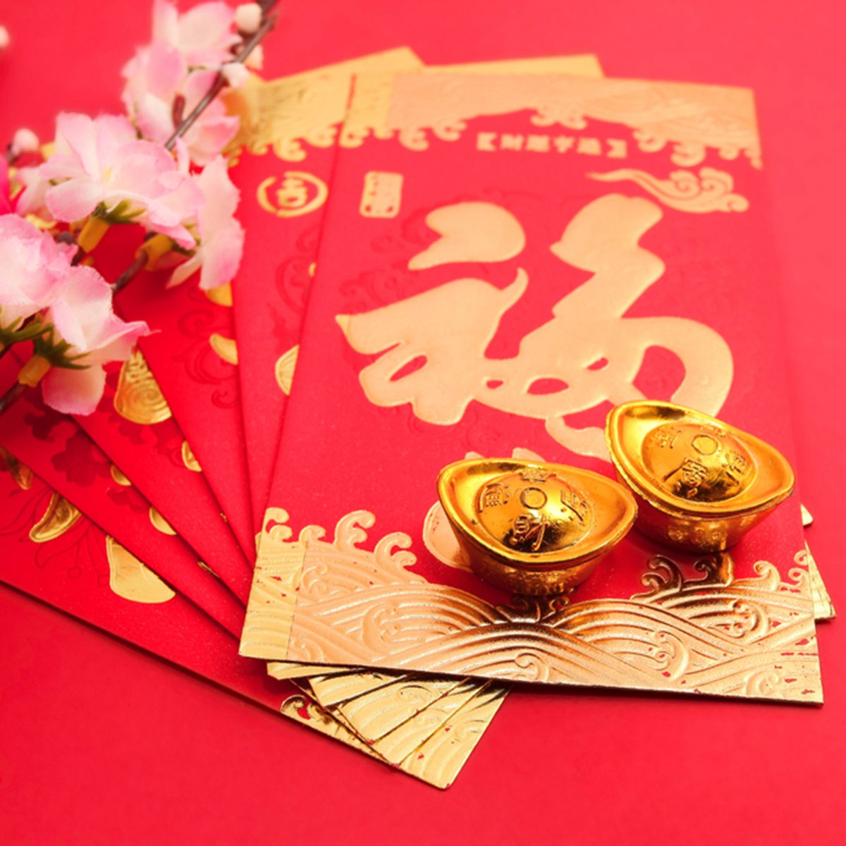 """Red packet (with Chinese character """"fu"""" means fortune) shoe-shaped gold ingot and Plum Flowers on red background with copy space; Shutterstock ID 250442641"""