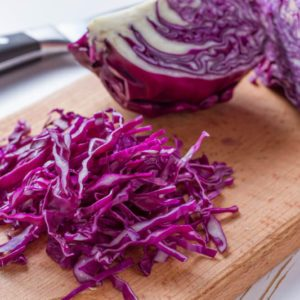 Red cabbage sliced on wood board, white wood background