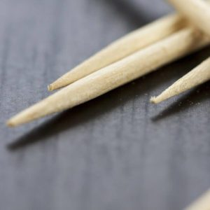 Pile of wooden toothpicks scattered randomly on a grey background for cleaning between the teeth after a meal in a personal hygiene concept