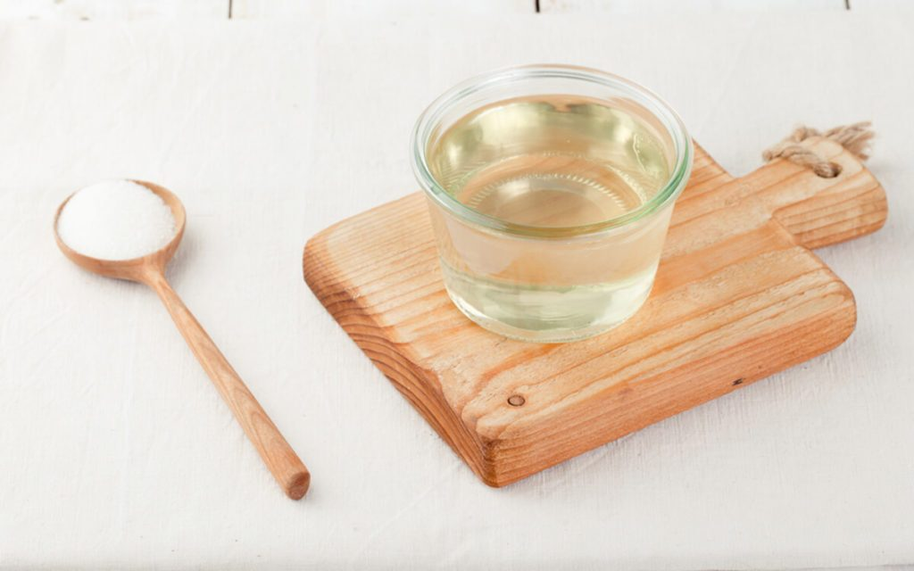 Sugar syrup in a glass bowl on a white wooden background, simple syrup