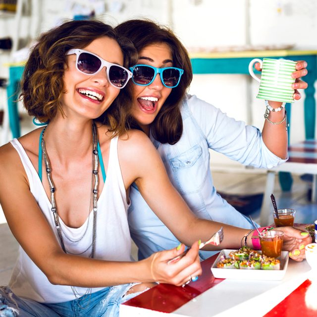 Two pretty best friend girls enjoy their lunch together in cute cafe, smiling speaking and gossip, bright clothes sunglasses, jewelry and accessorizes. portrait of women taking breakfast .; Shutterstock ID 287935583