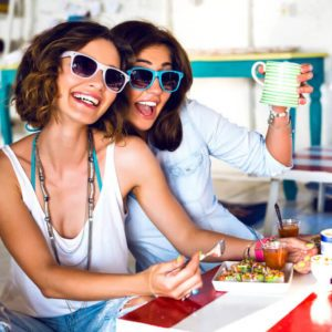 Two pretty best friend girls enjoy their lunch together in cute cafe, smiling speaking and gossip, bright clothes sunglasses, jewelry and accessorizes. portrait of women taking breakfast
