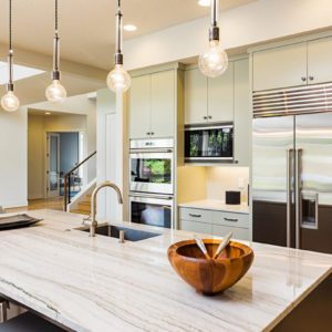 Kitchen Interior with Island, Sink, Cabinets, Stainless Steel Refrigerator, Pendant Lights, and Hardwood Floors