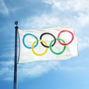 White Olympics Flag against the blue sky showing the rings of olympics logo. Illustrative editorial manipulation