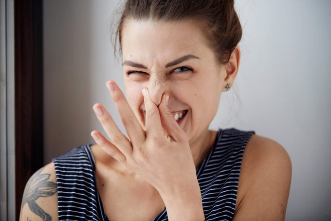 Headshot woman pinches nose with fingers hands looks with disgust something stinks bad smell situation.