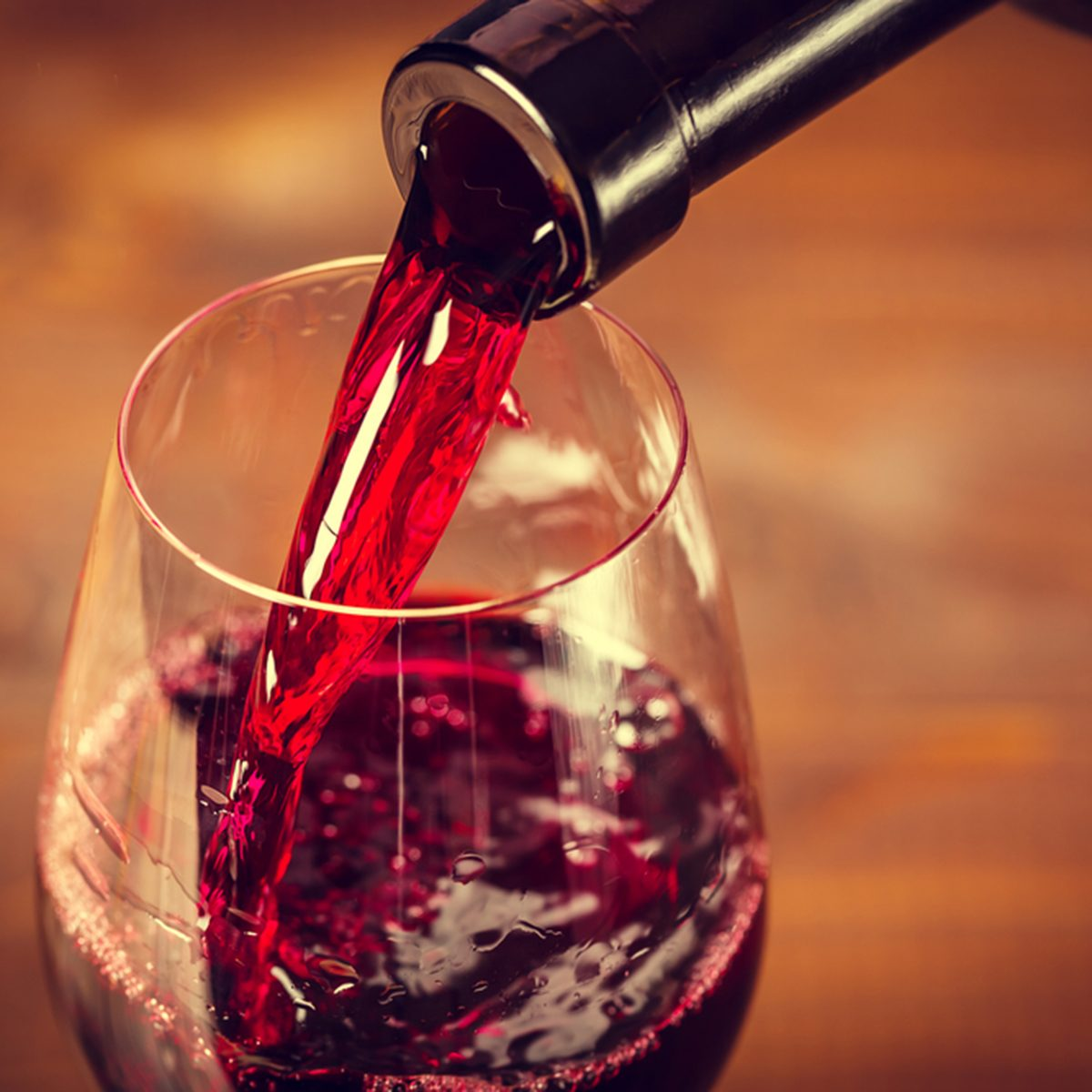 Pouring red wine into the glass against wooden background; Shutterstock ID 374546602; Job (TFH, TOH, RD, BNB, CWM, CM): TOH