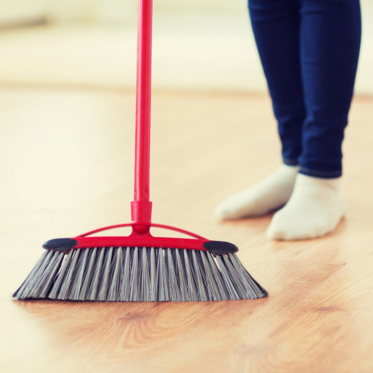 people, housework, cleaning and housekeeping concept - close up of woman legs with broom sweeping floor at home; Shutterstock ID 388206061