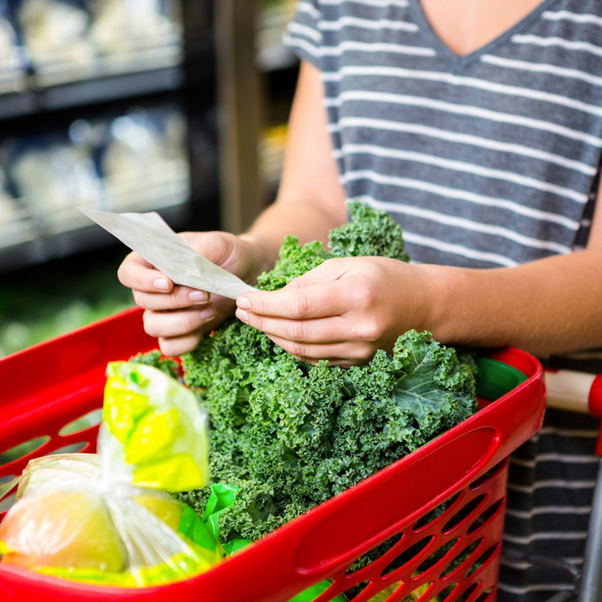 Woman with red basket holding list in supermarket; Shutterstock ID 398707321
