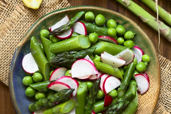 Fresh green asparagus, radish and pea salad served on plate, ingredients on the side, photographed overhead with natural light