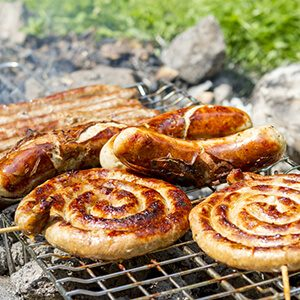 Sausages on grill outdoor. Grilling bratwursts on a charcoal grill