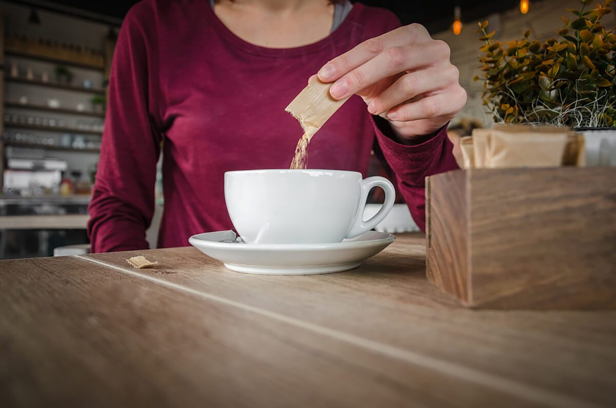 girl or woman chooses brown sugar and puts the coffee in a cafe