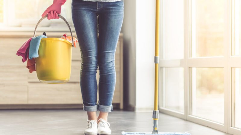 Cropped image of beautiful woman in protective gloves holding a flat wet-mop and bucket with detergents and rags while cleaning her house