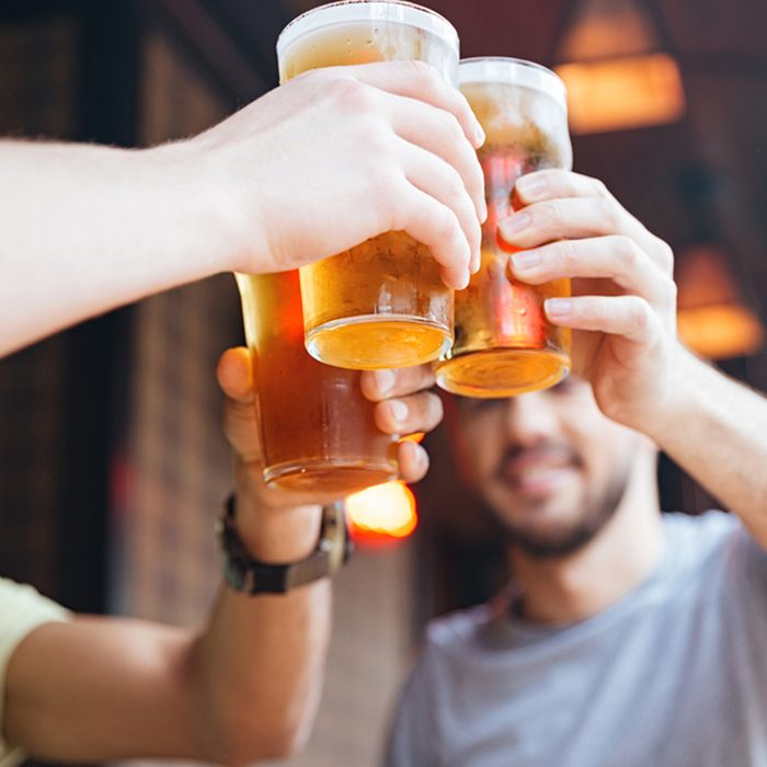Happy male friends clinking with beer mugs in pub; Shutterstock ID 521300353